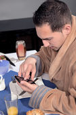 Man using his mobile at breakfast — Stock Photo