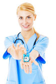 Nurse Showing Toy Alarm Clock Over White Background — Stock Photo