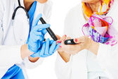 Doctor Examining Senior Woman's Blood Sugar Against White Backgr — Stock Photo