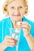 Senior mujer sosteniendo el vaso de agua y tabletas — Foto de Stock