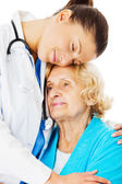 Doctor Embracing Senior Woman Over White Background — Stock Photo