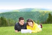 Ungt par och laptop i bergen — Stockfoto
