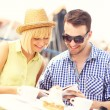 Young couple reading a guide in a restaurant — Stock Photo #47341051