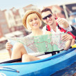 Young tourists with a map in a canoe — Stock Photo #47341127