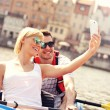 Young couple taking pictures in a canoe — Stock Photo #47341233