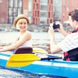 Happy tourists taking pictures in a canoe — Stock fotografie