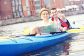 Happy tourists with a map in a canoe — Stock Photo