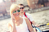 Young woman talking on the phone in a canoe — Stock Photo