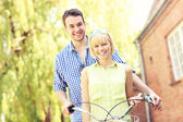 Happy couple on a bike — Stock Photo