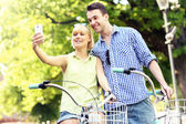 Happy couple taking pictures of themselves on a bike — Foto Stock