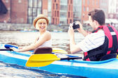 Happy tourists taking pictures in a canoe — Foto Stock