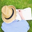 Woman taking notes on grass — Stock Photo #47836083