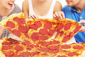 Group of friends with pizza — Stock Photo