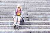 Woman with roller blades sitting on stairs — Stock Photo