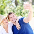 Young couple taking a picture of themselves at the beach — Stock Photo #50333411