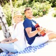 Romantic couple playing guitar at the beach — Stock Photo #50333457