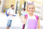 Pretty student showing ok sign in the campus — Stock Photo