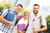 Group of happy students in front of modern buildingd — Stock Photo