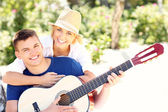 Joyful couple and guitar — Stock Photo