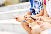 Sección media de los estudiantes y sus smartphones — Foto de Stock