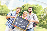 Group of students holding a back to school blackboard in the par — Stock Photo