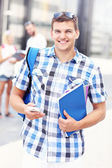 Happy student standing in the campus with his smartphone — Stock Photo