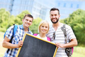Group of students holding a blackboard in the park — Stock Photo