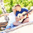Happy couple on the beach with guitar — Stock Photo #50423337