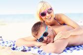 Couple sunbathing at the beach — Stockfoto
