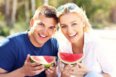 Happy couple with watermelon at the beach — Stockfoto