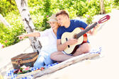 Happy couple on the beach with guitar — Stock fotografie