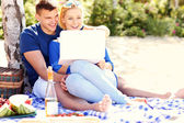 Happy couple with laptop at the beach — Stockfoto