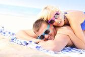 Joyful couple sunbathing at the beach — Stockfoto