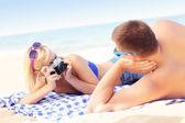 Vrouw nemen een foto van haar vriendje op het strand — Stockfoto