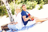 Romantic couple playing guitar at the beach — Стоковое фото