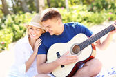 Romantic couple and guitar on the beach — Stock fotografie