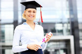 Happy graduate standing outside modern building — Stock Photo