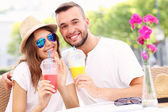 Happy couple drinking smoothies in an outside cafe — Stock Photo