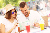 Beautiful couple looking at map in a cafe — Stock Photo