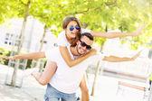 Joyful couple doing piggyback in the park — Stock Photo