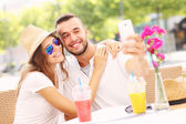 Happy couple taking selfie in a cafe — Foto Stock