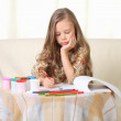Little blond girl drawing at home on sofa — Stock Photo #13606152