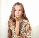 Little blond girl sends air kiss and blowing — Stockfoto
