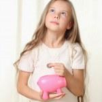 liten blond flicka sätter mynt i piggy Sparbössa och drömmer abo — Stockfoto