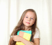 Little blond girl holding different books and smiling — Stock Photo