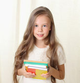 Little blond girl holding diffenet books and smiling — Stock Photo