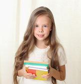 Liten blond flicka håller diffenet böcker och ler — Stockfoto