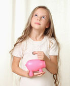 Little blond girl puts coin into piggy moneybox and dreaming abo — Stock Photo
