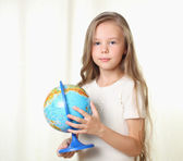 Little blond girl holding globe and looking on camera — Stock Photo