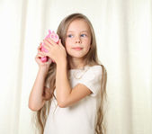 Little blong girl hearing how much money in piggy moneybox — Stockfoto